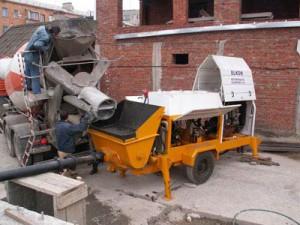 Миксер разгружается в силос бетононасоса